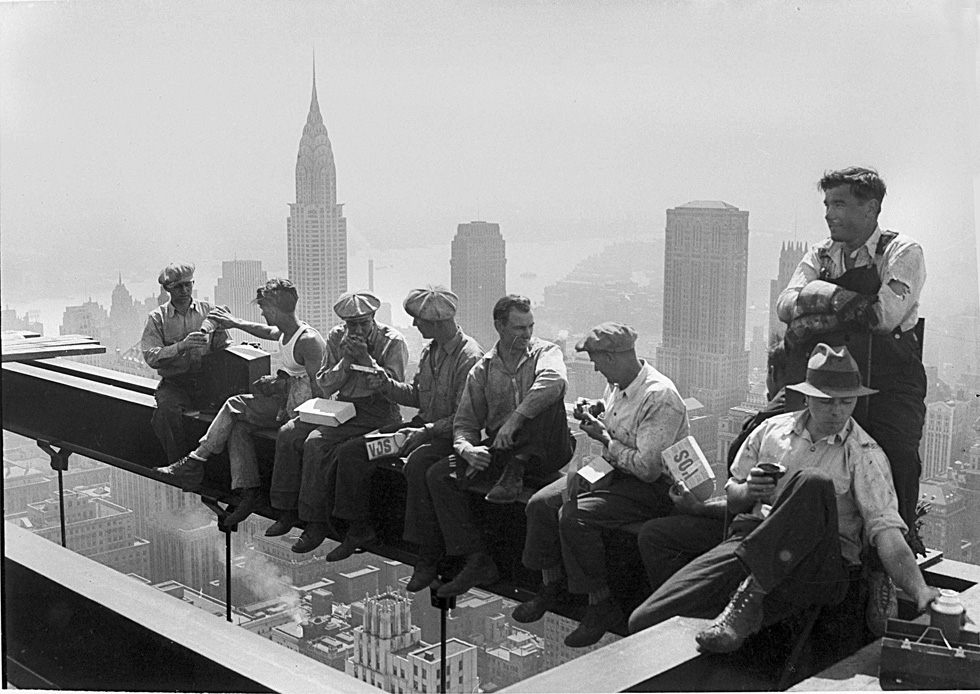 Construction workers take a lunch break on a steel beam atop the RCA Building at Rockefeller Center, New York, Sept. 29, 1932.  In the background is the Chrysler Building.  (AP Photo)