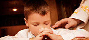 Young Boy Praying by Priest --- Image by © Con Tanasiuk/Design Pics/Corbis