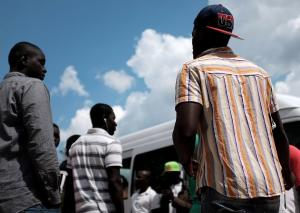 Migrants stand at the Cara Mineo, a hosting centre for asylum seekers, where about 3,200 migrants from North Africa, Ivory Coast, Pakistan, Syria, Afghanistan and other countries are staying in Mineo in the the province of Catania in Sicily on April 21, 2015, three days after a migrant boat capsized in the Mediterranean's deadliest disaster in decades. Only 28 people, including the two arrested men, survived the disaster on April 19, 2015 in which 800 people are feared to have drowned. Some of the survivors, who hailed from Mali, Gambia, Senegal, Somalia, Eritrea and Bangladesh, were recovering at the holding Cara Mineo centre.  AFP PHOTO / ALBERTO PIZZOLI        (Photo credit should read ALBERTO PIZZOLI/AFP/Getty Images)