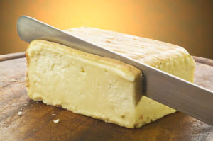 Taleggio cheese on cutting board sliced
